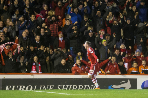 Aberdeen FC player celebrates in front of the Dons fans