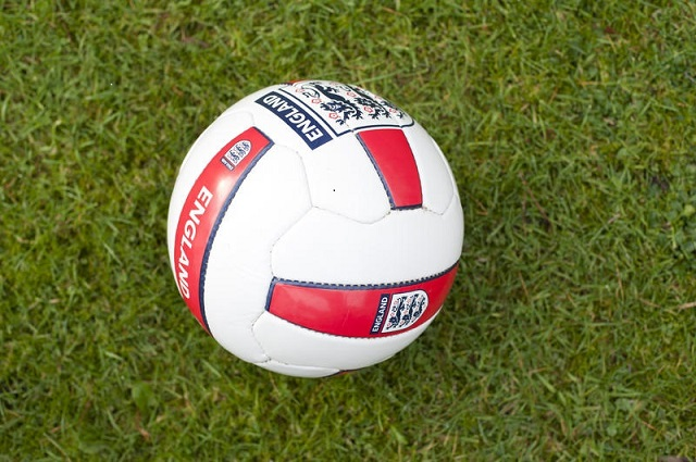 Football with Three Lions logo on grass background